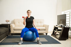 Cute Hispanic woman exercising at home. Wide view of a young Hispanic woman lifting weights while sitting on a stability ball at home Royalty Free Stock Photo