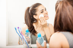 Cute Hispanic woman removing her makeup. Happy young Hispanic brunette using makeup remover with a cotton pad in the bathroom Stock Photos