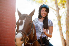 Cute horse rider smiling. Portrait of a pretty young woman taking a ride with her horse on a sunny day stock image