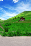 Cute house in Austria. Cute house located on the green mountain under beautiful blue sky stock photo