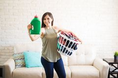 Cute housewife showing fabric softener bottle. Attractive maid holding detergent bottle for machine wash and clothes for wash in living room Royalty Free Stock Image