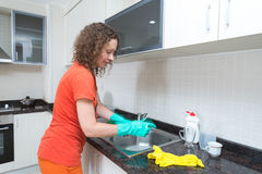 Cute housewife washing dishes with a sponge Royalty Free Stock Photos