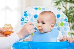 Cute hungry baby eating fruit mash Stock Image