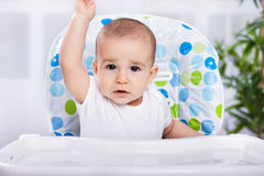 Cute hungry baby in kitchen chair ready for eat Royalty Free Stock Photography