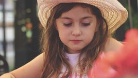 Cute hungry little girl with straw hat, smiling and eating her cheeseburger. Cute little girl with straw hat, smiling and eating her cheeseburger stock video footage