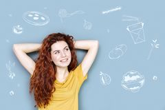 Cute hungry student smiling while thinking about tasty food. Hungry student. Pretty young woman having her hands behind her head and smiling while thinking about stock photo