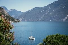Cute idyllic Italian village and lake captured from the water. Limone at lago di Garda. Idyllic coastline scenery in Italy, captured from the water. Blue water royalty free stock images