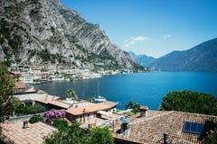 Cute idyllic Italian village and lake captured from the water. Limone at lago di Garda. Idyllic coastline scenery in Italy, captured from the water. Blue water royalty free stock image