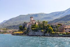 Idyllic coastline scenery in Italy, captured from the water. Blue water and a cute village at lago di garda, Malcesine. Cute idyllic Italian village and lake stock photography