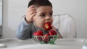 Cute impatient two years old baby boy cant wait to eat strawberries. Eating half of strawberry and than changing to another one stock footage