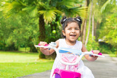 Cute Indian girl biking. At outdoor garden. Child having fun with bicycle Royalty Free Stock Photography