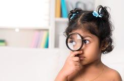 Cute Indian girl peeking through magnifying glass. Child at home. Cute Indian girl peeking through magnifying glass Stock Photography