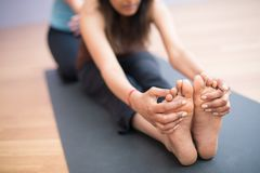 А cute Indian girl Yoga practitioner in a deep stretch, reachin Stock Image