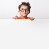 Cute infant. Photo of positive schoolkid behind partition looking at camera with smile Royalty Free Stock Photos