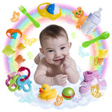 Cute infant baby with accessories in a rainbow. Composition of infant baby surrounded by  baby accessories in a rainbow Stock Image