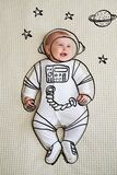 Cute infant baby girl sketched as astronaut stock photo