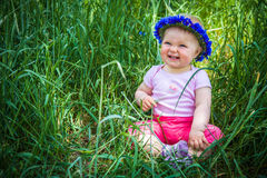 Cute infant baby in grass. Cute infant baby girl sitting in grass Stock Image