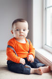 Cute infant baby in hat near window Royalty Free Stock Images