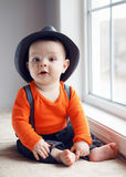 Cute infant baby in hat near window Royalty Free Stock Photo