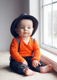 Cute infant baby in hat near window Royalty Free Stock Photos