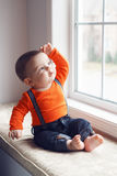 Cute infant baby in hat near window Stock Images
