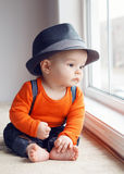 Cute infant baby in hat near window Stock Photos