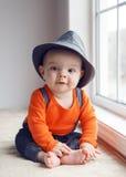 Cute infant baby in hat near window Stock Image