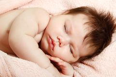 Cute infant baby sleeping, beautiful kid`s face closeup. Studio shot royalty free stock image
