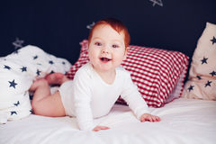 Cute infant baby waking up in his bed Stock Photo