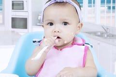 Cute infant bites a porridge spoon Stock Photography