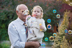 Cute infant blowing soap bubbles Stock Photo