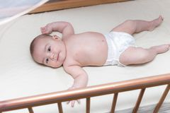 Infant boy is lying in a baby crib royalty free stock image