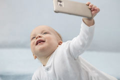 Cute infant boy makes selfie with a cell phone. Adorable smiling toddler kid taking a selfie photo with smartphone. Royalty Free Stock Images