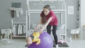 Cheerful mom training baby girl on fitball indoor stock footage