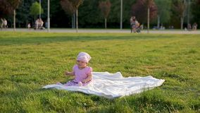 Cute infant girl sits on green grass in city park near with balloons then balloons fly away and her mom brings them back stock footage