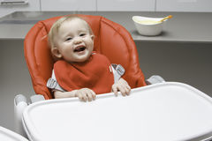 Cute infant girl sitting in baby chair and looking at camera Stock Photos
