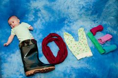 Cute infant laying in big black boot and towels, romper suit on blue background stock photo