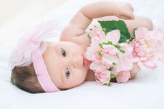 Cute infant lying in bed. Little princess. Close up of little infant lying in bed and holding pink flowers Stock Images
