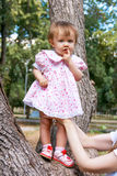 Cute infant in pink dress suckle finger stock images