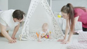 Cute infant playing in hut while parents crawling stock video footage