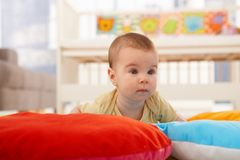 Cute infant on playmat. Cute infant crawling on playmat Royalty Free Stock Photo