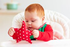 Cute infant redhead baby boy in elf costume playing with red star in highchair. At home Stock Photo