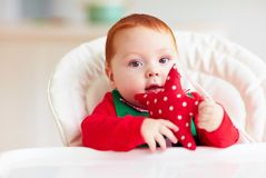 Cute infant redhead baby boy in elf costume sitting in highchair at home Royalty Free Stock Images