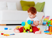 Cute infant redhead baby playing with toys at home Royalty Free Stock Photos