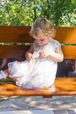 Cute infant sitting on bench Royalty Free Stock Images