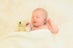 Cute infant sleeping together with teddy bear toy on bed home Royalty Free Stock Photo