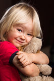 Cute injured boy hugging stuffed toy. A cute injured little blond boy hugs his stuffed toy and looks at camera Royalty Free Stock Photo