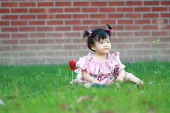 Cute innocent baby girl play on the lawn Stock Photo