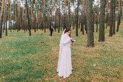 Cute innocent bride in white gown with fur halfcoat wait for her handsome groom on fores trail Royalty Free Stock Image