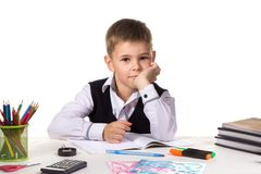 Cute intelligent pupil sitting at the desk with hand under the chin surrounded with stationery.  Stock Image